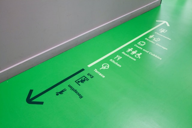 Placing the wayfinding on the floor frees up wall space for artwork.