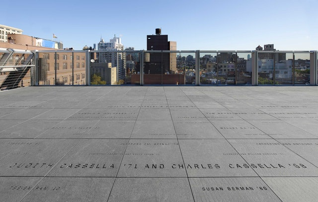 Donor signage on the roof terrace appears as a constellation of names engraved in granite.