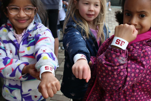 "Young Quaker fans power up with their new ""SF"" (Sidwell Friends) insignia wristbands."