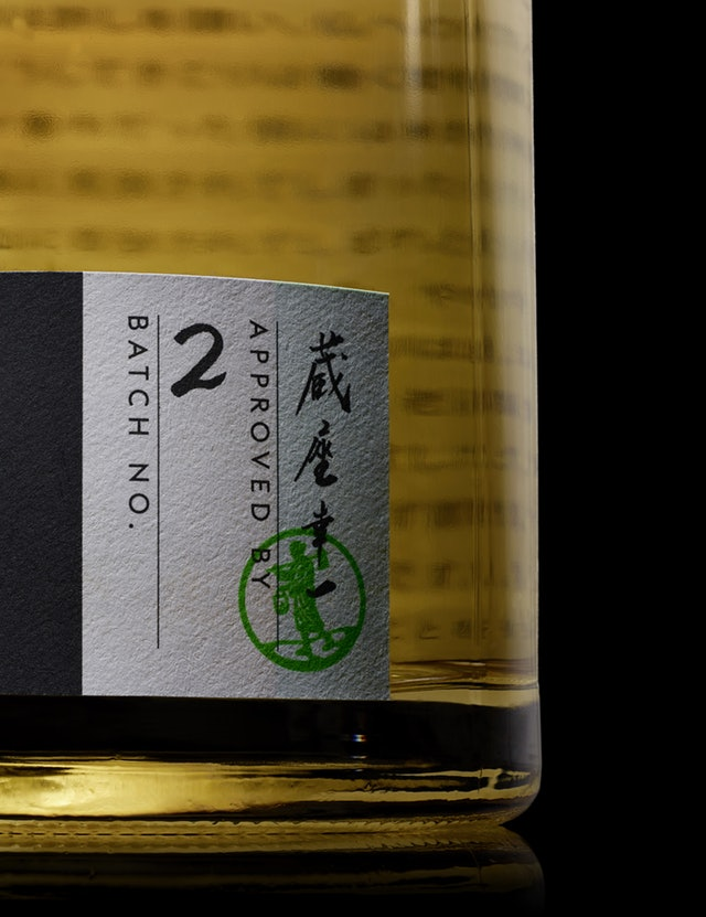The bottle's label includes the distiller's handwritten signature, the batch number and a stamp.